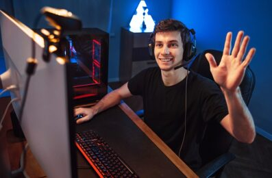 Professional cyber gamer having live stream, waving hand to followers and subscribers of his internet channel, recording vlog via webcam while playing online video game in room. Neon color background